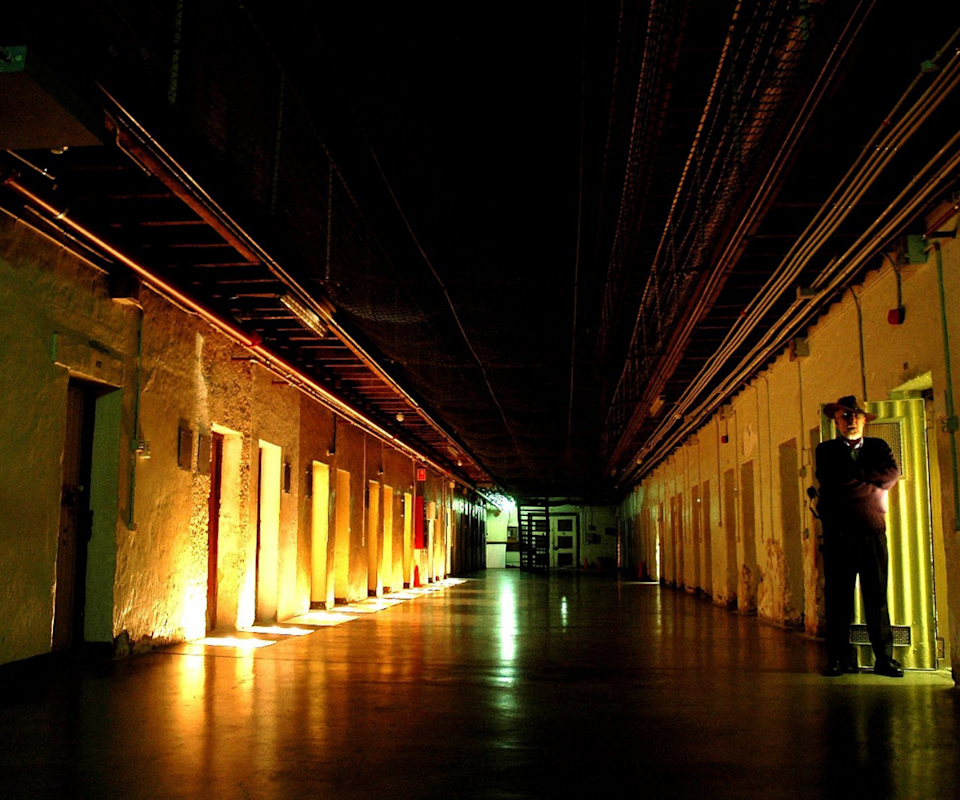 A dimly lit corridor in Fremantle Prison with a man on the right standing in a 19th-century suit.
