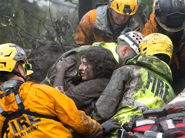 <p>Emergency personnel carry a woman rescued from a collapsed house after a mudslide in Montecito, Calif., Jan. 9, 2018. (Photo: Kenneth Song/Santa Barbara News-Press via Reuters) </p>