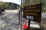 A parking reservation sign alerts visitors at the entrance to the Adirondack Mountain Reserve trailhead, Saturday, May 15, 2021, in St. Huberts, N.Y. A free reservation system went online recently to control growing numbers of visitors packing the parking lot and tramping on the trails through the private land of the Adirondack Mountain Reserve. The increasingly common requirements, in effect from Maui to Maine, offer a trade-off to visitors, sacrificing spontaneity and ease of access for benefits like guaranteed parking spots and more elbow room in the woods. (AP Photo/Julie Jacobson)