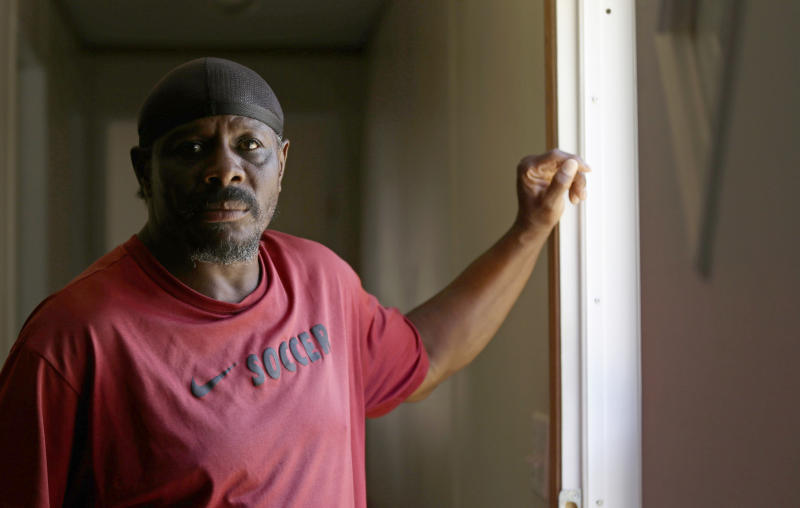 CORRECTS TO LESANE, NOT LESEUNE - In this photo taken Wednesday, May 29, 2019 resident James Lesane stands at the entrance to his mobile home in Lumberton, N.C. Every month, Lesane pays what he can afford for his mobile home lot rental_$150. But, after the Florida-based company Time Out Communities bought the park, he got a notice in the beginning of this year that his lot rent would be increasing to $465 a month. (AP Photo/Gerry Broome)