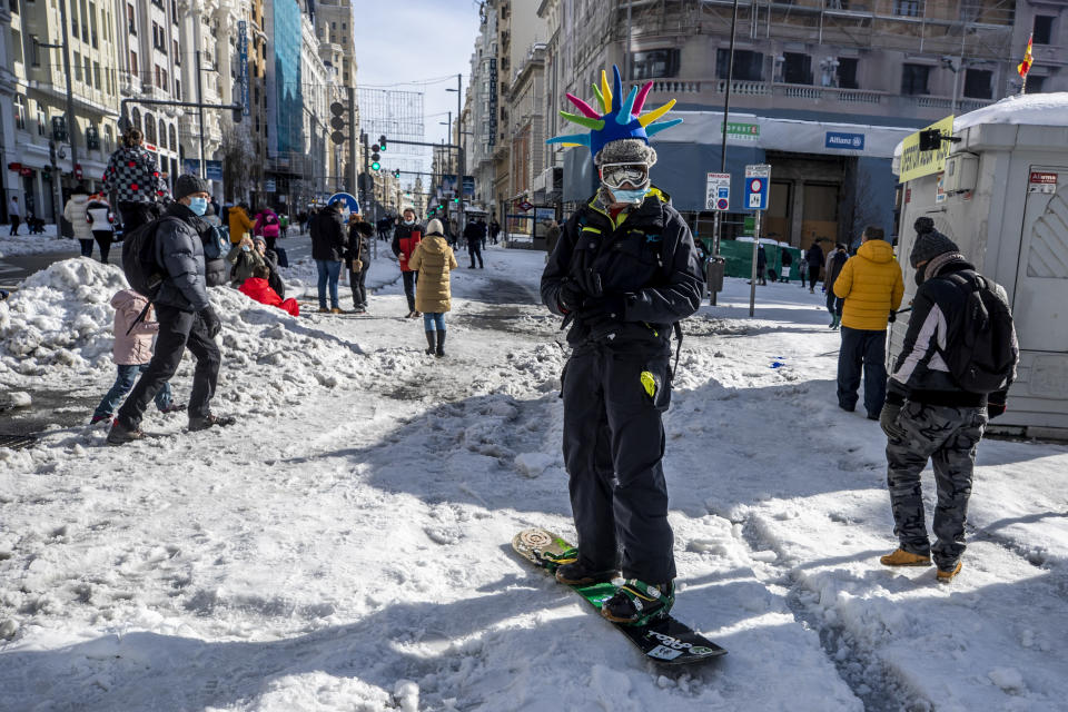 A man snowboards at the Gran Via avenue in downtown Madrid, Spain, Sunday, Jan. 10, 2021. A large part of central Spain including the capital of Madrid are slowly clearing snow after the country's worst snowstorm in recent memory. (AP Photo/Manu Fernandez)
