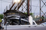 An emergency worker surveys the remains of a derailed Amtrak train in Philadelphia, Pennsylvania May 13, 2015. An Amtrak passenger train with more than 200 passengers on board derailed in north Philadelphia on Tuesday night, killing at least five people and injuring more than 50 others, several of them critically, authorities said. Authorities said they had no idea what caused the train wreck, which left some demolished rail cars strewn upside down and on their sides in the city's Port Richmond neighborhood along the Delaware River. REUTERS/Lucas Jackson