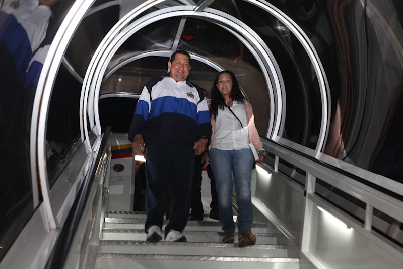 """CORRECTS NAME OF DAUGHTER TO VIRGINIA -- In this photo provided by Miraflores Presidential Press Office, Venezuela's President Hugo Chavez, left, accompanied by his daughter Rosa Virginia, smiles upon his arrival to Caracas, Venezuela, Wednesday April 11, 2012. Chavez returned to Venezuela and said he's """"doing well"""" following cancer treatment in Cuba. Chavez flew to Cuba last week for his third round of radiation therapy. (AP Photo/Miraflores Presidential Office)"""
