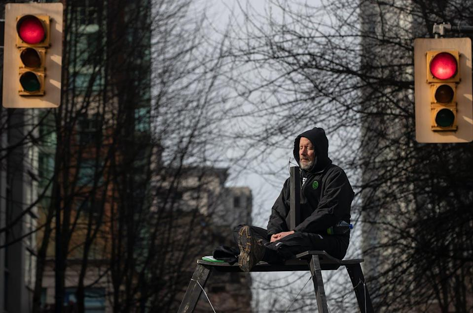 """<span class=""""caption"""">A person sits on a tripod platform high above the street as protesters occupy an intersection during a demonstration to call for government action to on climate change in Vancouver in February 2021. </span> <span class=""""attribution""""><span class=""""source"""">THE CANADIAN PRESS/Darryl Dyck</span></span>"""