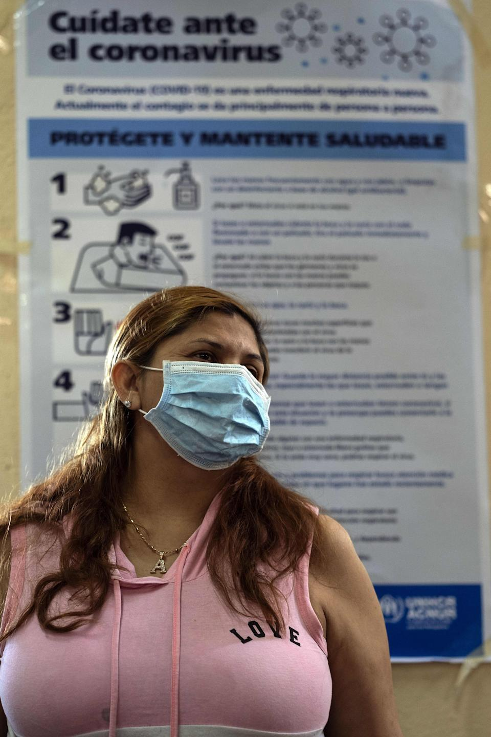 An asylum seeker wears a face mask near a poster with information on the prevention of COVID-19, at the Juventud 2000 migrant shelter in Tijuana, Baja California State, Mexico, on April 3, 2020 during the novel coronavirus pandemic. - Thousands of migrants overcrowding shelters or begging in the streets in Mexican cities along the US border are living in fear as the novel coronavirus spreads in the population and screening interviews for asylum seekers are being suspended. (Photo by Guillermo ARIAS / AFP) (Photo by GUILLERMO ARIAS/AFP via Getty Images)