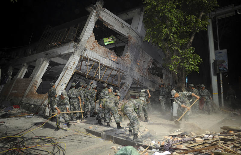 Rescue workers clear debris from a collapsed building after an earthquake jolted Yingjiang county in southwestern China's Yunnan Province on Friday, March 11, 2011.  The earthquake toppled more than 1,000 houses and apartment buildings in China's southwest near the border with Myanmar, killing at least 25 people and injuring 250, the government said Friday. (AP Photo) CHINA OUT