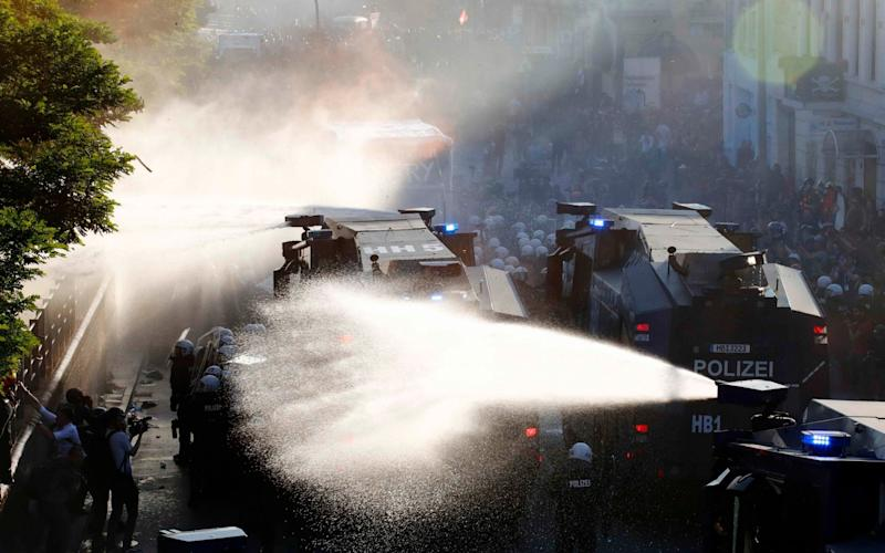 German riot police use water cannons against protesters during the demonstrations during the G20 summit in Hamburg - Credit: Reuters
