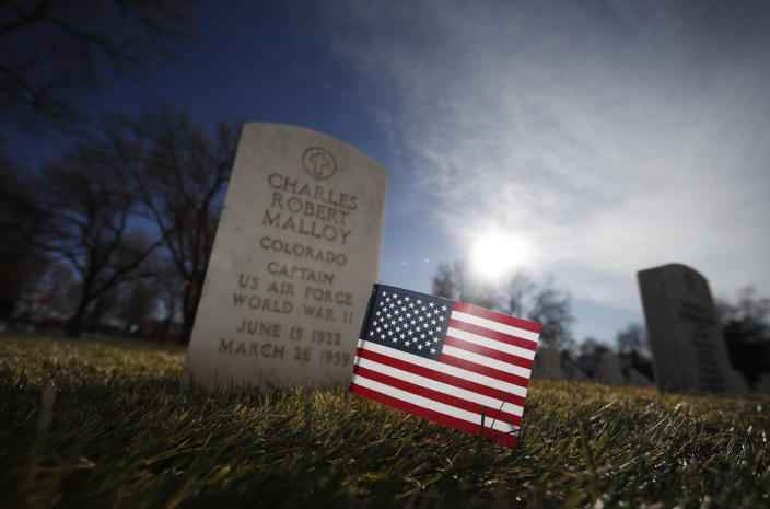 An American flag stands near the stone at the grave of U.S. Air Force Capt. Charles Malloy to mark Veterans Day in Fort Logan National Cemetery, Nov. 10, 2019, in Sheridan, Colo. (Photo: David Zalubowski/AP)