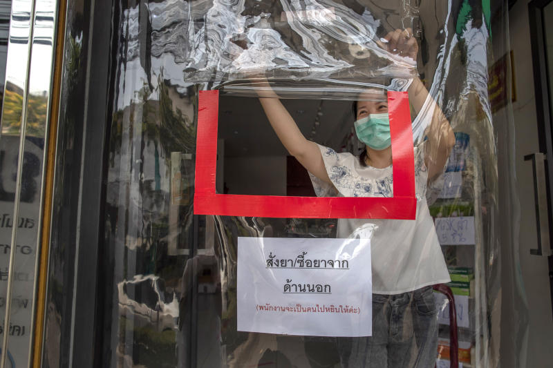 A pharmacist opens a service window through a plastic sheet covering the entrance to help practice social distancing in Bangkok, Thailand, Thursday, April 2, 2020. A state of emergency has been declared in the country to allow the government to impose stricter measures to control the coronavirus that has infected hundreds of people in the region. The new coronavirus causes mild or moderate symptoms for most people, but for some, especially older adults and people with existing health problems, it can cause more severe illness or death. (AP Photo/Gemunu Amarasinghe)