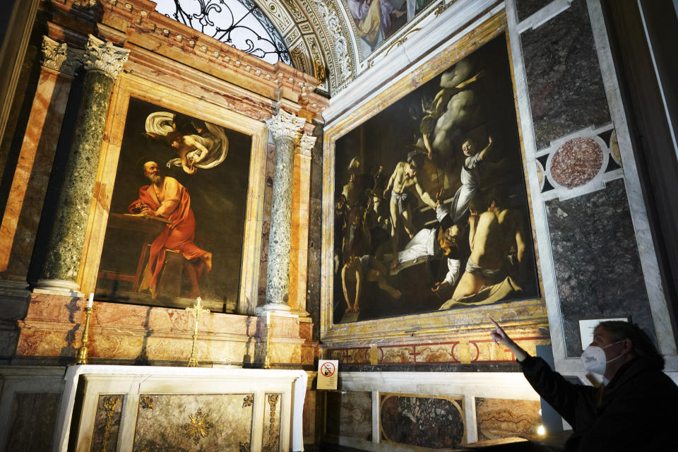 A woman wearing a face mask to curb the spread of COVID-19 points to a cycle of paintings by 16th century artist Michelangelo Merisi, known as Caravaggio, on the life of St.Matthew, inside the Contarelli chapel of San Luigi dei Francesi Church, in Rome, Friday, Dec. 11, 2020. Like elsewhere in Europe, museums and art galleries in Italy were closed this fall to contain the spread of COVID-19, meaning art lovers must rely on virtual tours to catch a glimpse of the treasures held by famous institutions such as the Uffizi in Florence and the Vatican Museums in Rome. However, some exquisite gems of Italy's cultural heritage remain on display in real life inside the country's churches, some of which have collections of renaissance art and iconography that would be the envy of any museum. (AP Photo/Andrew Medichini)