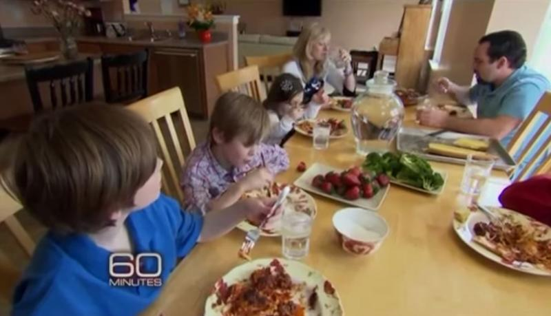 Michael and Kristine Barnett eating dinner with four kids at the table in 2012 during a segment for 60 Minutes.