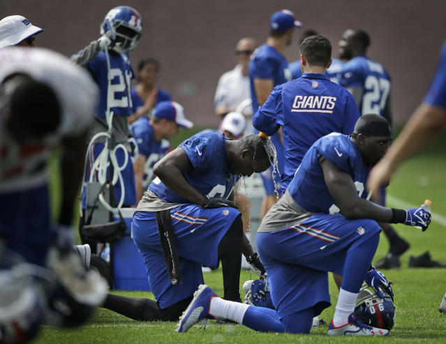New York Giants players try to keep cool during a NFL football camp in East Rutherford, N.J., Wednesday, July 23, 2014. (AP Photo/Seth Wenig)