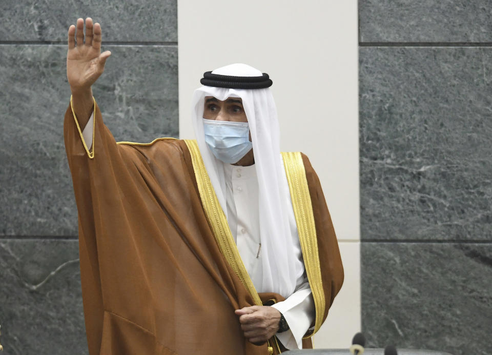 FILE - In this Sept. 30, 2020 file photo, the new Emir of Kuwait Sheikh Nawaf Al Ahmad Al Sabah, waves after he was sworn in at the Kuwaiti National Assembly. Kuwait, one of the world's wealthiest countries, is facing a debt crisis as a parliamentary election looms in December. It needs the new parliament to approve raising its debt spending and passing the bill will be the first legislative challenge for the new emir. (AP Photo/Jaber Abdulkhaleg, File)