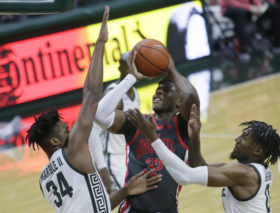 Ohio State forward E.J. Liddell (32) shoots against Michigan State forwards Julius Marble II (34) and Aaron Henry, right, during the first half of an NCAA college basketball game Thursday, Feb. 25, 2021, in East Lansing, Mich. (AP Photo/Duane Burleson)