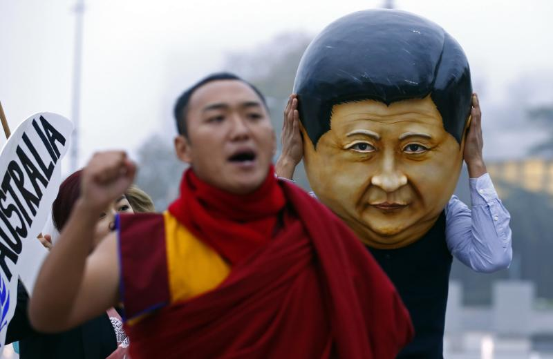 Protester wearing a giant head representing China's President Xi Jinpig takes part in a demonstration calling Xi out for rights violations in Tibet in Geneva
