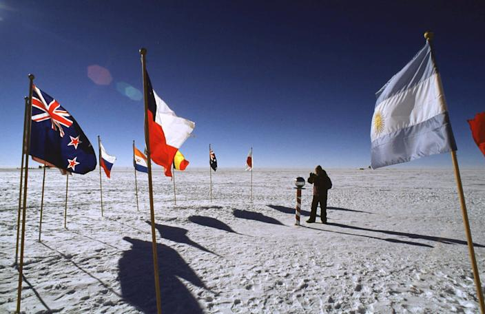 Flags of some of the 43 countries that have signed treaties protecting the South Pole and Antarctica flank the ceremonial marker at the South Pole in December 1997. A new study released June 29, 2020, said the South Pole is warming at over three times the global rate over the past 30 years.