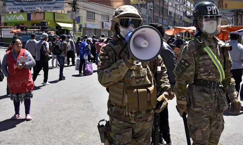 A military policeman uses a loudspeaker to tell people to go home during a total lockdown in El Alto, Bolivia, on 3 April.