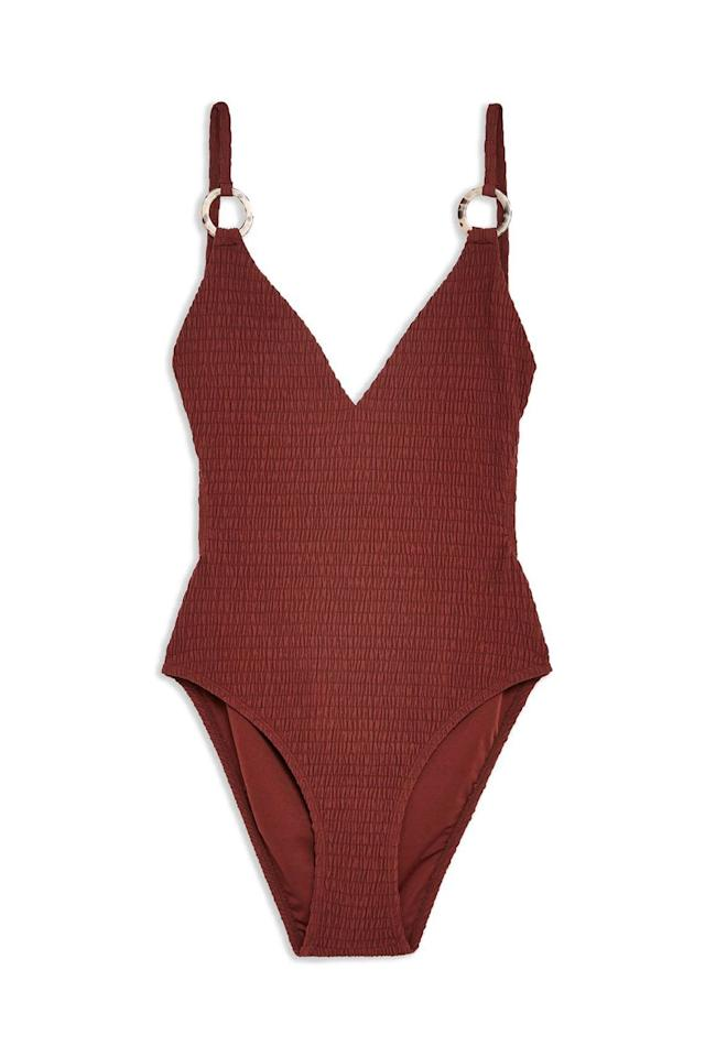"""<p><strong>Topshop</strong></p><p>topshop.com</p><p><strong>$52.00</strong></p><p><a href=""""http://us.topshop.com/en/tsus/product/burgundy-shirred-ring-swimsuit-8750366"""" target=""""_blank"""">SHOP IT</a></p><p>This affordable swimsuit has cutouts all over and a ring detail on the straps for that not-too-simple look. You'll notice the one piece isn't completely smooth either because it's made with a shirred material. Trade in your black swimsuit STAT for this baby.</p>"""