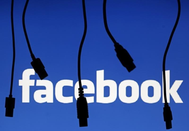 Electronic cables are silhouetted next to the logo of Facebook in this illustration photo in Sarajevo