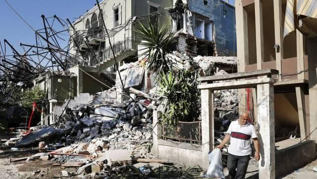 A Lebanese man carries his belongings as he leaves his destroyed house near the scene where an explosion hit on Tuesday the seaport of Beirut, Lebanon. AP
