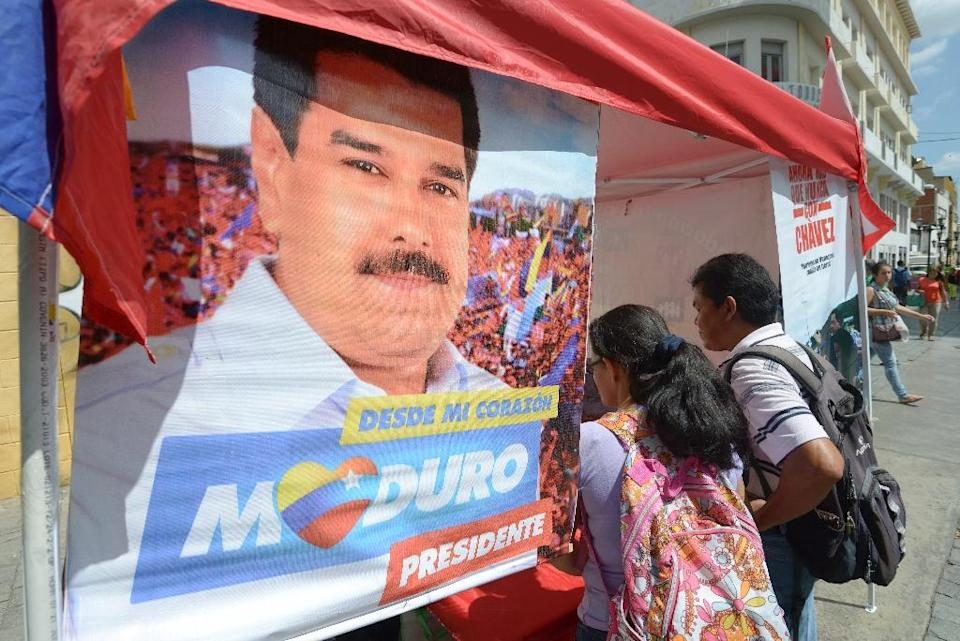 Venezuela's opposition has been hoping to capitalize on the unpopularity of Nicolas Maduro, pictured in poster, to win control of the National Assembly in the December 6 polls (AFP Photo/Juan Barreto)