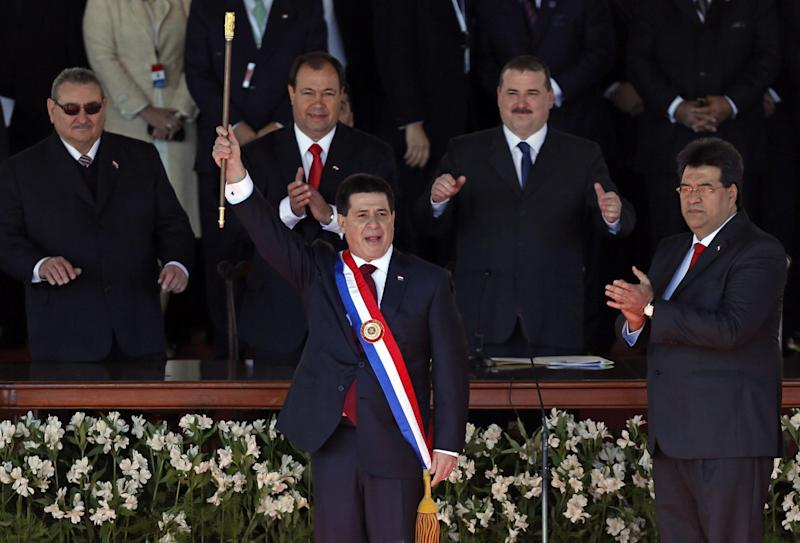 """Paraguay's new President Horacio Cartes, center, holds up the presidential baton as Congress President Julio Cesar Velazquez, right, applauds at his swearing-in ceremony at Palacio de Lopez presidential palace in Asuncion, Paraguay, Thursday, Aug. 15, 2013. Paraguayan multimillionaire Horacio Cartes promised that """"the fatherland comes first"""" in his inaugural speech as president on Thursday, delivering a powerful message in one of the most unequal nations in South America. (AP Photo/Jorge Saenz)"""