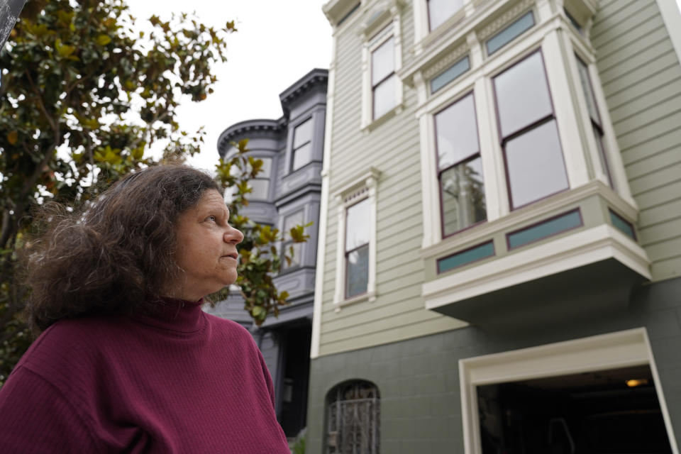 Census taker Linda Rothfield looks up at an apartment building she was unable to access in San Francisco, on Wednesday, June 30, 2021. Some census takers worry that renters in apartment buildings were not tallied fully during the nation's head count last year. Census takers say they had difficulty entering apartment buildings due to COVID restrictions, and they weren't able to get in touch with landlords for help. (AP Photo/Eric Risberg)