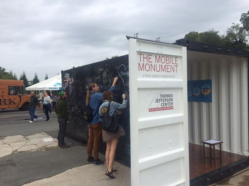 """<a href=""""http://tjcenter.org/free-speech-monuments/"""" target=""""_blank"""">The Mobile Monument Project</a>is a roving installation that beganin2015. Theshipping container's outside is a chalkboard on which participantscan express themselves freely. The inside is an evolving gallery of First Amendment history, which is updated to incorporate specific cases relevant to each of the mobile monument's destinations and audiences. (Clay Hansen)"""