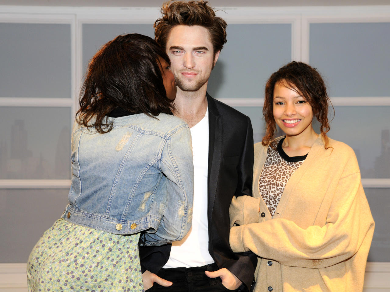 Visitors pose for a photograph with a wax figure of British actor Robert Pattinson in a VIP section of Madame Tussauds London, after being installed for the first time, in London March 25, 2010.   REUTERS/Madame Tussauds London/Handout