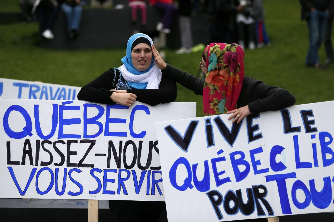 "Women hold signs as they protest against Quebec's proposed Charter of Values in Montreal, September 14, 2013. Thousands took to the streets to denounce the province's proposed bill to ban the wearing of any overt religious garb by government paid employees. The signs read (L) ""Quebec let us serve you"" (R) ""freedom in Quebec for all"". REUTERS/ Christinne Muschi(CANADA - Tags: POLITICS CIVIL UNREST RELIGION)"