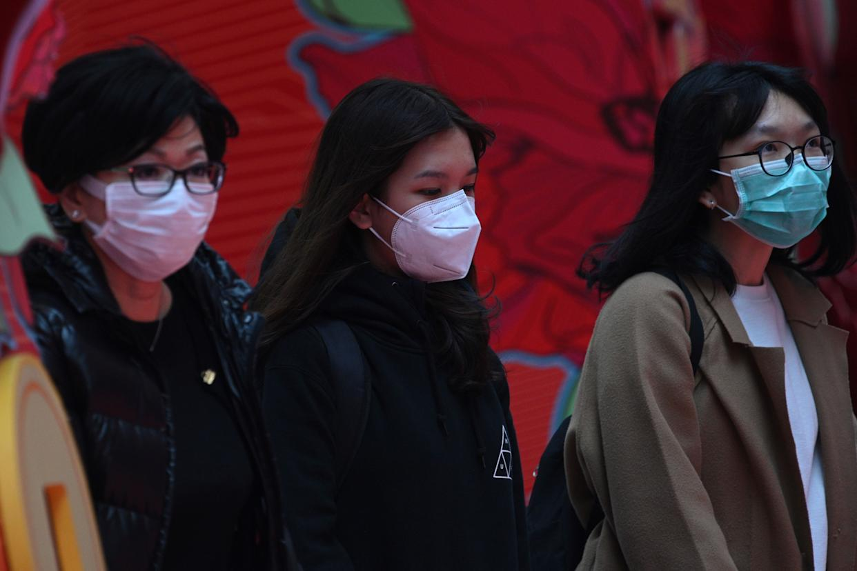 Pedestrians wear face masks in Hong Kong on February 5, 2020, as a preventative measure following a virus outbreak which began in the Chinese city of Wuhan. - More Chinese cities hunkered down by fencing off streets and telling millions of people to stay home as the death toll from the new coronavirus soared to nearly 500 on February 5. Hong Kong now has 18 confirmed infections, the majority people who were infected in mainland China. (Photo by Anthony WALLACE / AFP) (Photo by ANTHONY WALLACE/AFP via Getty Images)