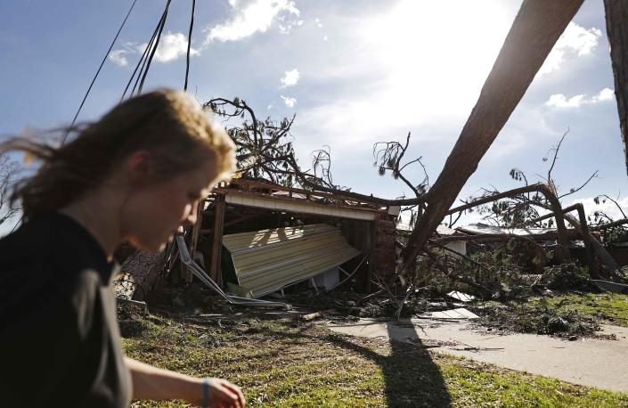 <p>Kelsey Gronbeck walks past damaged homes after checking on a friend's house in the aftermath of hurricane Michael in Callaway, Fla., Thursday, Oct. 11, 2018. (Photo: David Goldman/AP) </p>