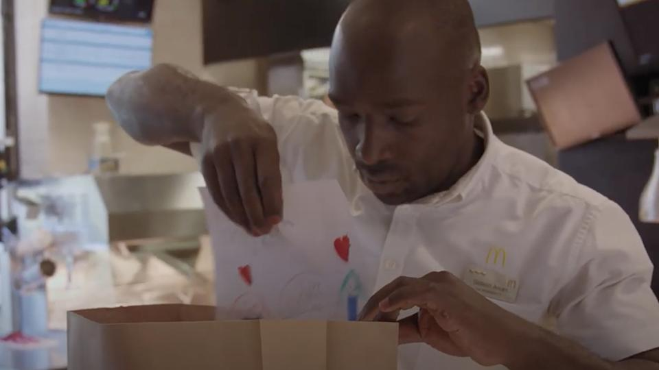 A McDonald's worker places a child's drawing into a delivery bag.