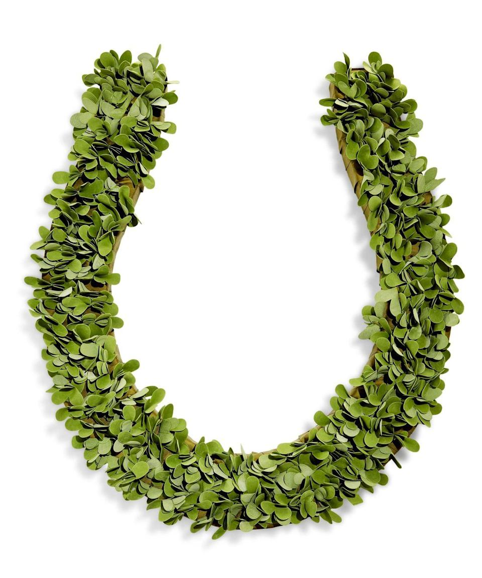"<p>Wrap a foam horseshoe-shaped wreath form in green ribbon. Cut bundles of greenery from a green foliage garland with wire cutters. Poke holes through ribbon into the foam with an awl; insert greenery. No wreath form? Simply cut a horseshoe shape from a piece of cardboard and cover with greenery from your yard.</p><p><a class=""link rapid-noclick-resp"" href=""http://thecraftplace.com/specialty-shapes/Emblems/horseshoe-emblem-24-quot-x-2-quot-thick-white-styrofoam"" rel=""nofollow noopener"" target=""_blank"" data-ylk=""slk:SHOP HORSESHOE WREATH FORM"">SHOP HORSESHOE WREATH FORM</a></p>"