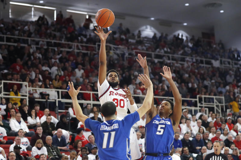 Creighton guard Marcus Zegarowski (11) and guard Ty-Shon Alexander (5) defend as St. John's guard LJ Figueroa (30) shoots a three-pointer during the second half of an NCAA college basketball game, Sunday, March 1, 2020, in New York. St. Johns upset Creighton 91-71. (AP Photo/Kathy Willens)
