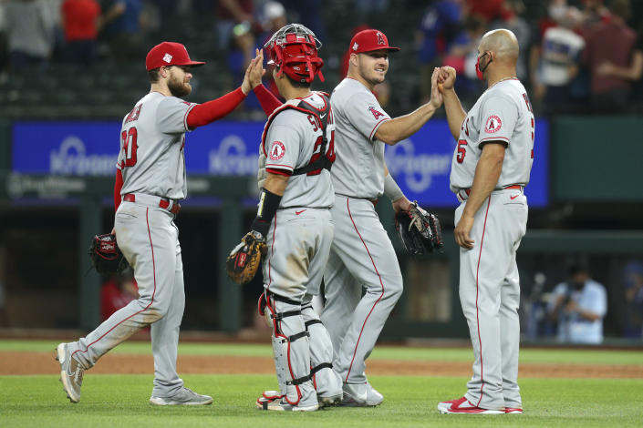 Los Angeles Angels Jared Walsh (20), Kurt Suzuki (24), Mike Trout (27), and Albert Pujols (5) celebrate the win over the Texas Rangers during a baseball game on Monday, April 26, 2021, in Arlington, Texas. (AP Photo/Richard W. Rodriguez)
