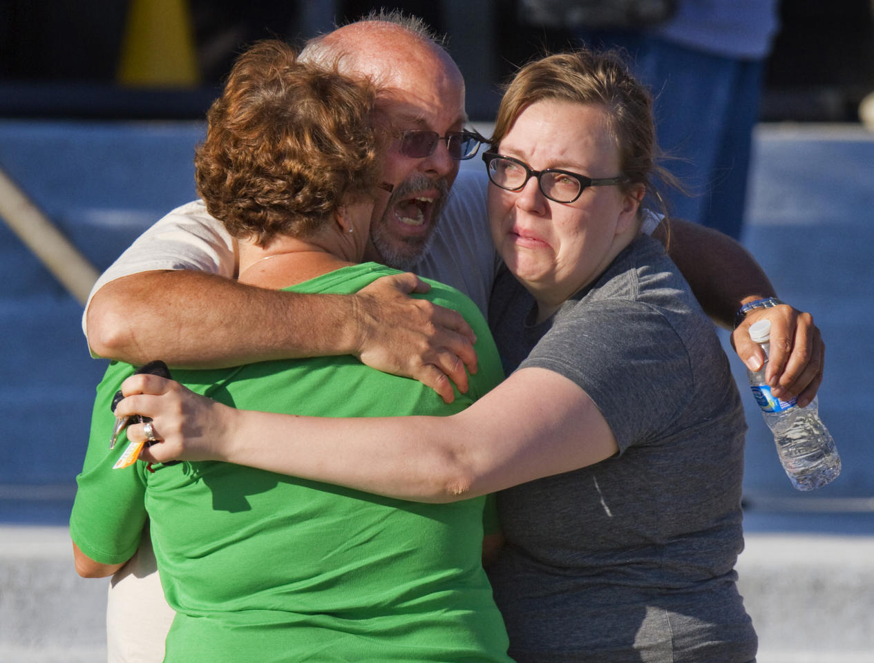 "Tom Sullivan, center, embraces family members outside Gateway High School where he has been searching franticly for his son Alex Sullivan who celebrated his 27th birthday by going to see ""The Dark Knight Rises,"" movie where a gunman opened fire Friday, July 20, 2012, in Aurora, Colo. (AP Photo/Barry Gutierrez)"