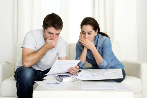 Couple looking at sheet of paper and covering mouths as if gasping