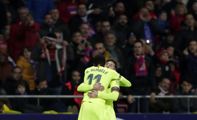Barcelona's Ousmane Dembele, front, celebrates with Lionel Messi after scoring his side's opening goal during a Spanish La Liga soccer match between Atletico Madrid and FC Barcelona at the Metropolitano stadium in Madrid, Saturday, Nov. 24, 2018. (AP Photo/Manu Fernandez)