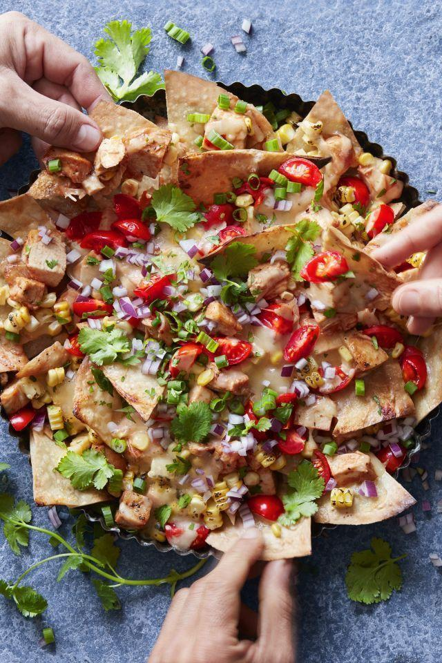 """<p>This BBQ chicken nachos recipe from <em>The Dude Diet </em>chef and author Serena Wolf is a total Game Day touchdown. Thanks to a few simple swaps, these nachos have half the calories, fat, saturated fat, sodium, and carbs of a typical serving.</p><p><span class=""""redactor-invisible-space""""><a href=""""https://www.womansday.com/food-recipes/recipes/a57709/fiesta-bbq-chicken-nachos-recipe/"""" rel=""""nofollow noopener"""" target=""""_blank"""" data-ylk=""""slk:Get the BBQ Chicken Nachos recipe."""" class=""""link rapid-noclick-resp""""><em>Get the BBQ Chicken Nachos recipe.</em></a></span></p>"""