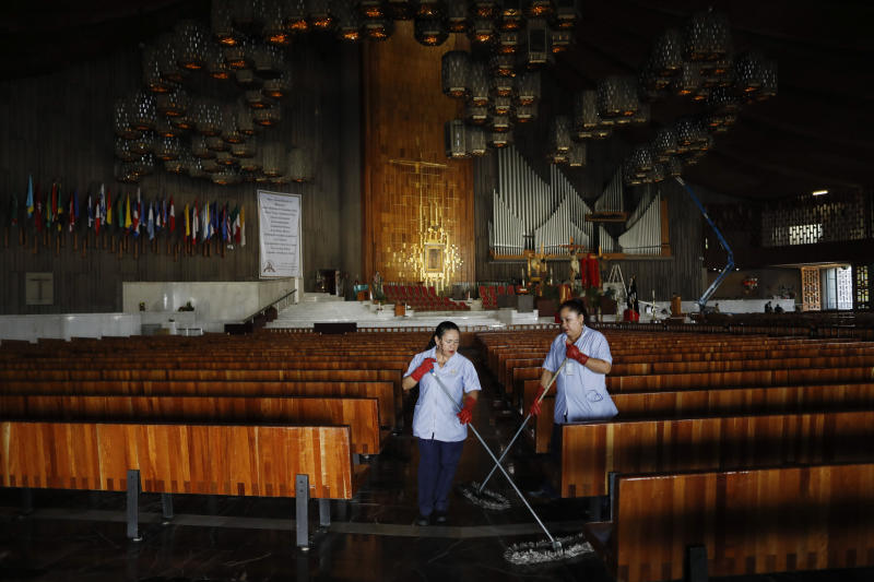 Cleaning staff mop the floor of the Basilica of Our Lady of Guadalupe, which was closed to the public to prevent the spread of coronavirus, in Mexico City, on Good Friday, April 10, 2020. Instead of celebrating with the usual packed churches and elaborate processions attended by thousands, this year Mexico's Catholic faithful were told to stay home, with closed-door Masses and a private performance of the Stations of the Cross broadcast on television. (AP Photo/Rebecca Blackwell)
