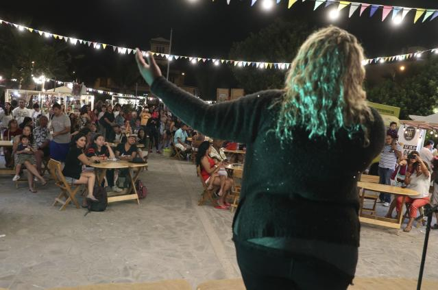 """In this Jan. 12, 2019 photo, Venezuelan singer Reymar Perdomo performs at a fair on the beach in San Bartolo, Peru. Perdomo combines her street performances with appearances at concerts and on TV programs, and her song """"Me Fui,"""" or """"I Left,"""" has become the unofficial anthem of Venezuelans who have fled their country's economic implosion. (AP Photo/Martin Mejia)"""