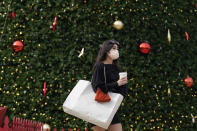 A woman wears a mask as she carries a shopping bag in front of the annual Macy's Great Tree at Union Square during the coronavirus outbreak in San Francisco, Saturday, Nov. 21, 2020. (AP Photo/Jeff Chiu)