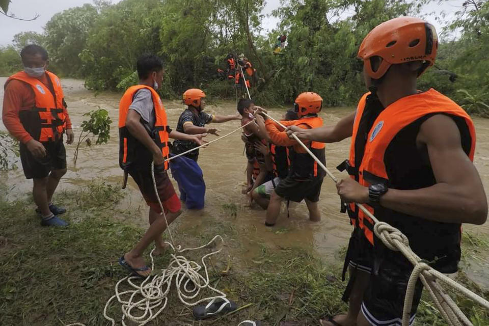 In this photo released by the Gonzaga Municipal Disaster Risk Reduction and Management Office, rescuers carry a child along a swollen river caused by heavy rains from Tropical Storm Kompasu in Gonzaga town, Cagayan province, northern Philippines on Monday Oct. 11, 2021. A number of people have been killed and others were reported missing in landslides and flash flood set off by a storm that barreled through the tip of the northern Philippines overnight then blew away Tuesday, officials said. (Gonzaga MDRRMO via AP)