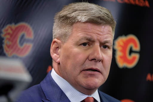 FILE - In this April 23, 2018, file photo, new Calgary Flames NHL hockey team head coach Bill Peters speaks to the media in Calgary, Alberta. Calgary Flames general manager Brad Treliving said the team is looking into an accusation that head coach Bill Peters directed racial slurs toward a Nigerian-born hockey player a decade ago in the minor leagues, then arranged for the players demotion when he complained. Akim Aliu tweeted Monday, Nov. 25, 2019, that Peters dropped the N bomb several times towards me in the dressing room in my rookie year because he didnt like my choice of music. (Jeff McIntosh/The Canadian Press via AP, File)