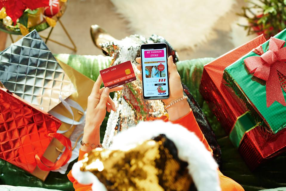 Holiday season. female in sparkle gold sequin santa hat with credit card browsing high fashion retail online store and on a smartphone while sitting on divan in the modern living room at Christmas.