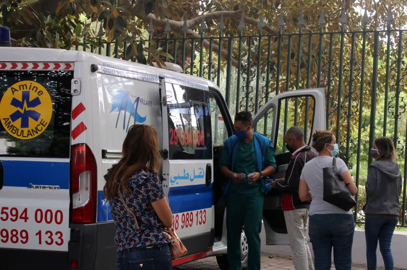 People wait to get tested for COVID-19 outside a mobile testing lab in Tunis