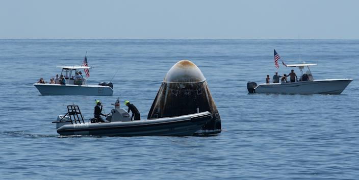 <br>Support teams and recreational boaters arrive at the SpaceX Crew Dragon Endeavour spacecraft shortly after it landed with NASA astronauts Bob Behnken and Douglas Hurley onboard in the Gulf of Mexico off the coast of Pensacola, Florida, on Sunday, Aug. 2, 2020.