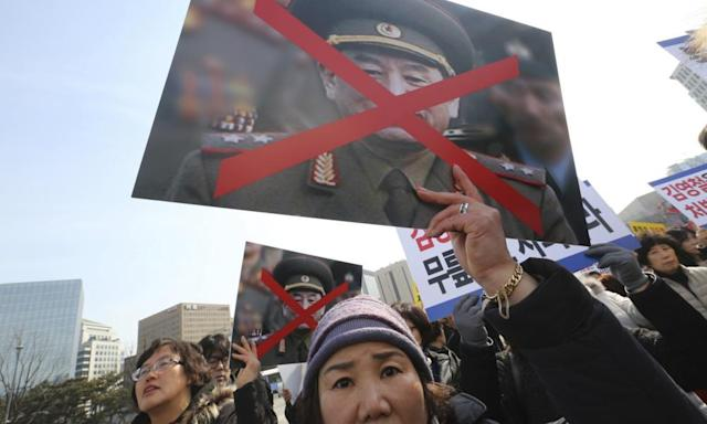 """<span class=""""element-image__caption"""">Family members of victims of the sunken South Korean naval ship Cheonan march with defaced portraits of Kim Yong-chol in Seoul on Saturday.</span> <span class=""""element-image__credit"""">Photograph: Ahn Young-joon/AP</span>"""