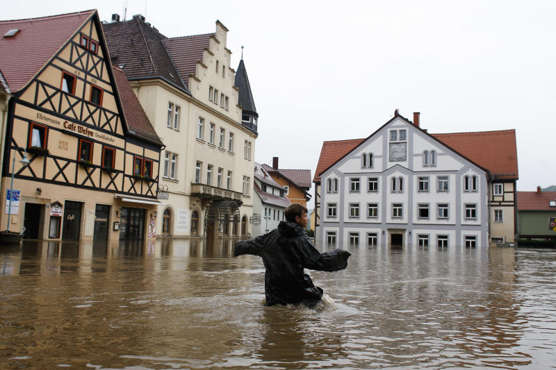 Rudolf (11) crosses the flooded market place of the city of Wehlen at river Elbe, Germany, Tuesday, June 4, 2013. After heavy rainfalls, swollen rivers flooded areas in Germany, Austria , Switzerland and Czech Republic. (AP Photo/Markus Schreiber)